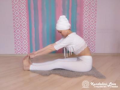 Удерживание наклона, ухватившись руками за пальцы ног. Упражнение Кундалини Йоги картинка